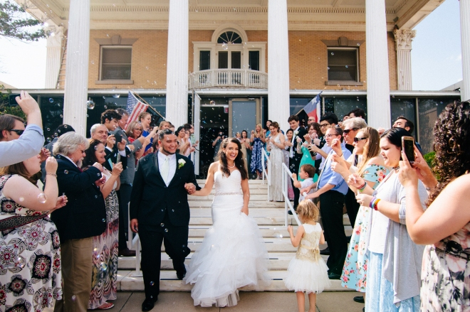 bride and groom exit the museum while guests blow bubbles-1