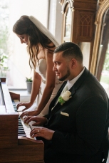 bride and groom play piano together close up-1