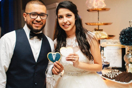 bride and groom hold their special cookies