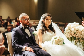 bride and groom sit as they listen to minister during ceremony