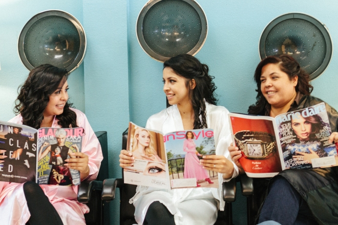 bride reads magazines with mom and sister under salon dryers