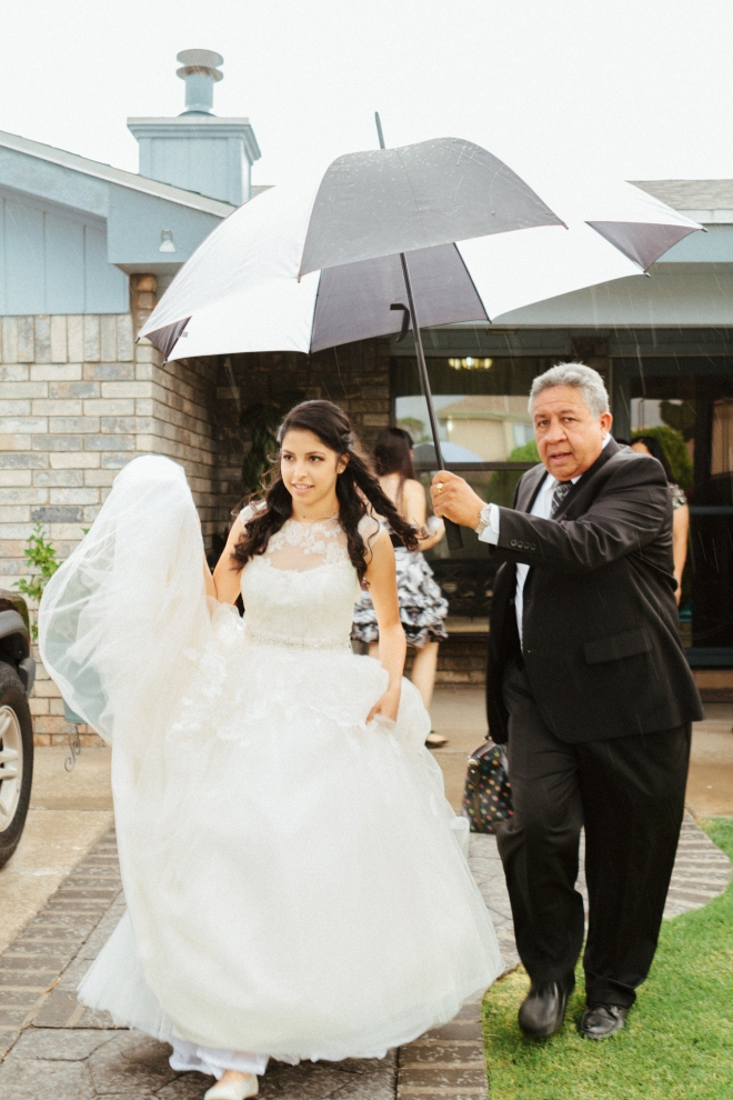 brides father sheilds her from the rain