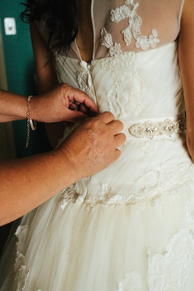 brides mother fastens dress