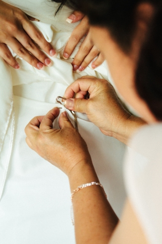 brides mother pins jewelry to her dress