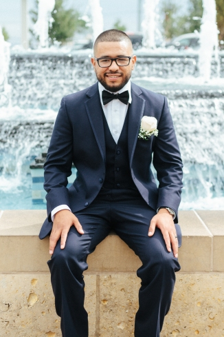 groom sits in front of fountain