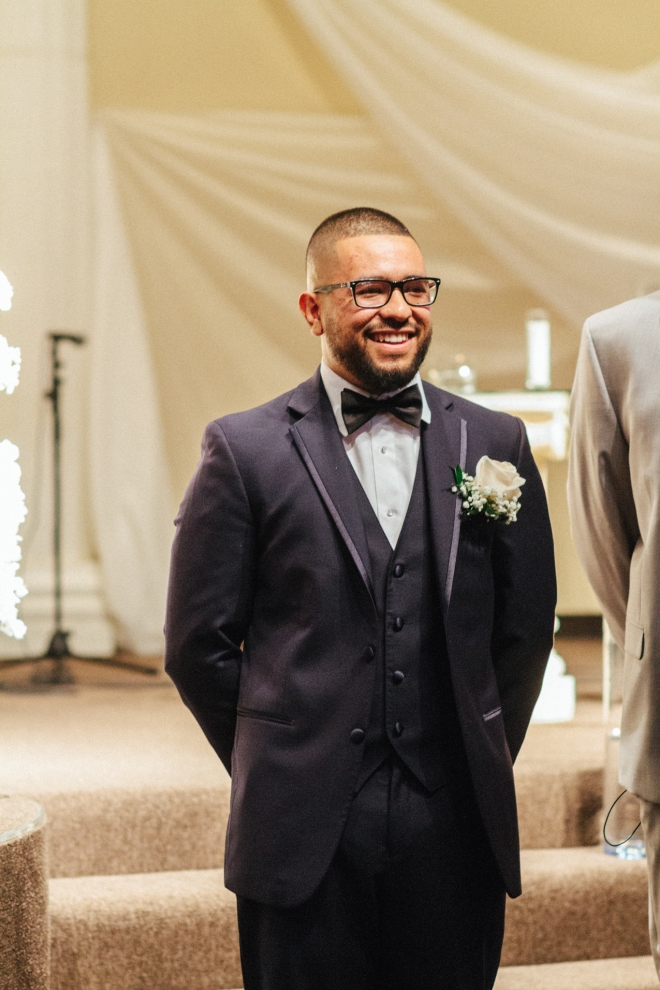 groom smiles as he waits for his bride at the altar