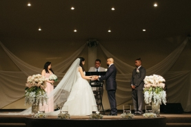 wide shot of bride and groom praying during ceremony